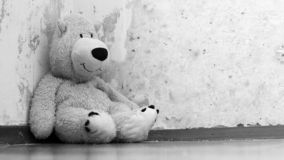Soft toy bear sitting on the floor. Old wall background, black and white mage stock photo
