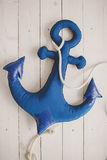 Soft toy blue anchor on wooden beams Stock Photos