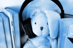 A soft toy bunny wearing too big headphones. Surrounded by books. royalty free stock photography