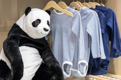 Soft toy panda bear on the background of children`s clothing stock image