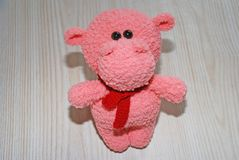 Soft toy pink Hippo stands on the table. Toy knitted handmade master stock image