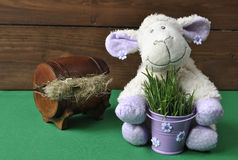 Soft toy sheep. With a bucket in which the green grass Royalty Free Stock Photos