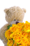 Soft toy teddy bear with a bouquet of yellow roses Royalty Free Stock Image