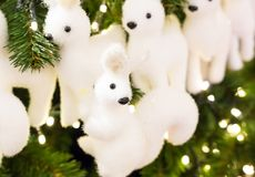 Soft toy white fir-tree felted squirrel with black eyes on a spruce christmas tree stock image