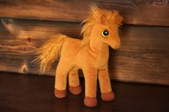 Soft toy on wooden background. Horse royalty free stock image