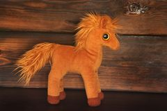 Soft toy on wooden background. Horse stock images