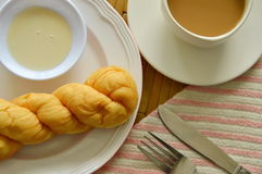 Soft twist bread dipping with sweetened condensed milk and coffee cup Royalty Free Stock Photo