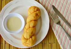 Soft twist bread dipping with sweetened condensed milk Stock Photos