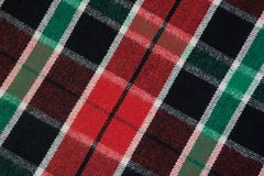Soft checkered wool blanket. Green and red plaid texture, macro shot. Wool plaid pattern. Textured surface of checkered cloth. Soft and warm checkered wool Stock Image
