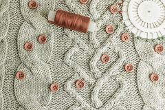 Soft warm natural sweater, fabrics with a knitted pattern of yarn and red small round buttons for sewing and a skein of red thread royalty free stock photos