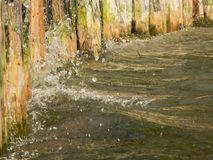 Soft water on the shore. Close-up water to a wooden shore attachment at the Lake Caldaro Stock Photography