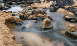Soft waters dark stones & sand stock images