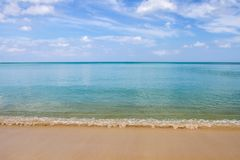 Soft wave on beach of blue ocean and sky. Background Stock Photos