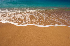 Soft wave of blue ocean on sandy beach. Background Stock Photography