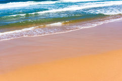 Soft wave of blue water on sandy beach. Seascape background Royalty Free Stock Photos