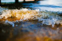 Soft wave reaching the pebble beach macro. Splashes of waves in sunlight stock photo