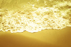 Soft wave of the sea on the sandy beach. In shades of yellow Royalty Free Stock Photo