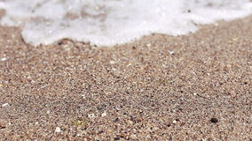 Soft wave of sea on sandy beach, sunny day. Close-up shooting, selective focus. Soft wave of sea on sandy beach, sunny day. Close-up shooting, selective focus stock footage