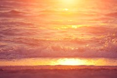 Soft wave of sea at sunset. Soft wave of sea on sandy beach at warm gold sunset light. Selective focus Royalty Free Stock Image