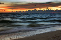 Soft waves and fiery sky. A colorful sunset creates the backdrop for the waves rolling into the shore at the beach Stock Photos