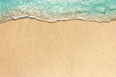 Soft waves with foam of blue ocean on the sandy beach.  royalty free stock images