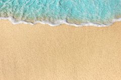 Soft waves with foam of ocean on the sandy beach background.  stock images