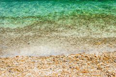 Soft waves with foam of water on pebbles and sandy beach.  royalty free stock photos