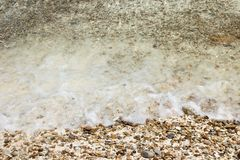 Soft waves with foam of water on pebbles and sandy beach.  stock photo