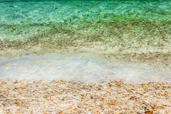 Soft waves with foam of water on pebbles and sandy beach.  stock photography