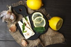 Soft white cheese with spices and lemons on a dark background. Rustic style royalty free stock photo