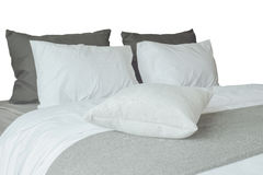 Soft white pillows and comfortable bed on white background Stock Image