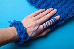 Soft woolen yarn and thread for knitting blue. The hand touches the material.  stock images