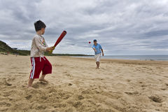 Softball. Father and son playing softball on beach Royalty Free Stock Photography