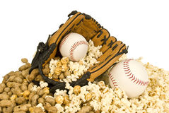 Softball, Baseball, and Snacks. A baseball glove holds a hardball, peanuts, and popcorn.  It sits on a mound of peanuts and popcorn and a softball Royalty Free Stock Image