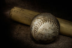 Softball and Bat. A worn softball and bat sit atop a burlap surface.  Image was lit by using a lightpainting technique Stock Photo
