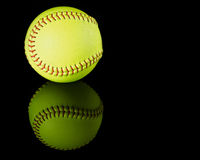 Softball on black reflective background. Royalty Free Stock Image