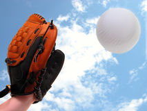 Softball Catch. Girl�s hand in a softball mitt about to catch a ball.  Motion blur on the softball Royalty Free Stock Image