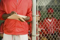 Softball coach writing on paper Stock Image