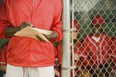 Softball coach writing on paper Stock Image