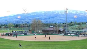 Softball game. Players on field during softball game in park with mountain backdrop stock footage