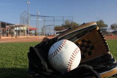 Softball with glove in the outfield Stock Images