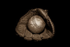 Softball and Glove in Sepia. A worn softball sits inside an old baseball glove on a solid black background.  Image was lit by using a lightpainting technique Stock Photo
