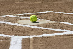 New Softball at home plate. A softball sitting on the home plate with fresh chalk lines Royalty Free Stock Photos