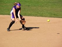 Softball Player. A girl softball player going for a grounder Royalty Free Stock Image