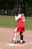 Softball player on base. Young girl softball runner at first base Stock Photos