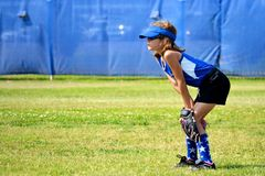 Softball Player Ready for the Next Play. She is playing right field in a ready position Royalty Free Stock Images