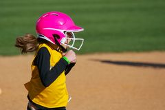 Softball Player Running Looking Surprised at the Play. Softball Player is running to third base. She has a surprised look on here face as she looks toward the Royalty Free Stock Images