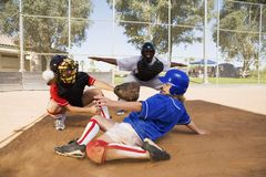 Softball player slideing. Into home plate Royalty Free Stock Images
