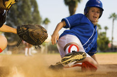 Softball Player Sliding Into Home Plate. Full length of softball player sliding into home plate Royalty Free Stock Photography