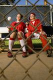 Softball players sitting on bench Stock Photos